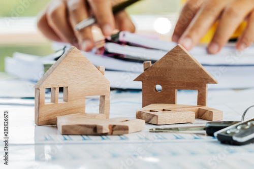 Obraz na plátne  Businessman hands signing documents file paperwork financial or property mortgage real estate investment business on desk office with chart report document contact customer with wooden house models
