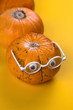 canvas print picture - funny autumn card pumpkin with eyes and glasses on a yellow background