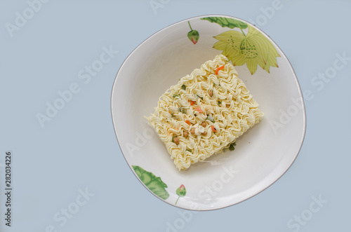 On the plane of the table is a plate with a dry briquette of pasta for quick preparation of meals, close-up Canvas-taulu