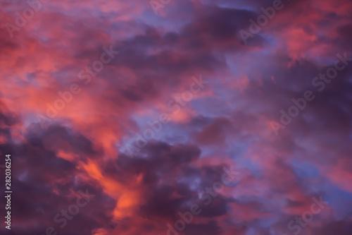 Foto auf Leinwand Hochrote The bright orange sun rises against the backdrop of purple clouds