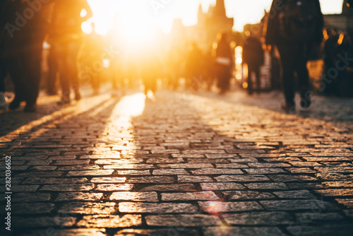 Busy European street at the sunset. People are blurred with a lens. Old pavement.