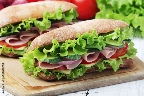 Keuken foto achterwand Snack Two sandwiches with fresh vegetables, ham and cheese in ciabatta bread