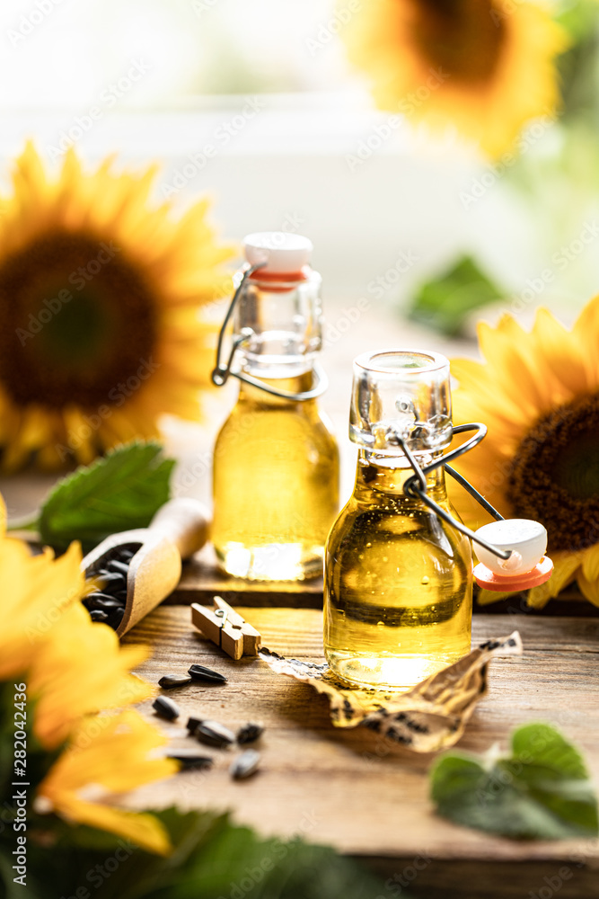 Fototapety, obrazy: Sunflower oil in a bottle glass with seeds and flowers of sunflower. on blurred background