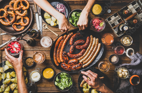Fényképezés  Flat-lay of Octoberfest dinner table concept with grilled sausages, pretzel past