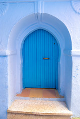 Typical, old, blue intricately carved, studded, Moroccan riad door and door-frame and old house. Beautiful view of the blue city in the medina. painted houses in CHEFCHAOUEN, MOROCCO