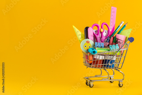 Poster de jardin Montagne Shopping cart with School stationery on yellow background.