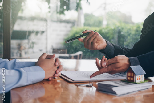 Fotografía  real estate agent holding house key to his client after signing contract,concept