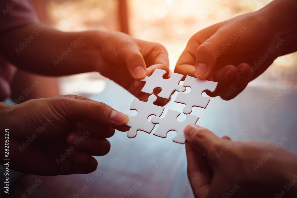 Fototapeta Closeup hand of business people connecting jigsaw puzzle with sunlight effect, Business solutions and represent team support and help concept, success and strategy concept