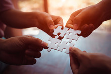 Closeup Hand Of Business People Connecting Jigsaw Puzzle With Sunlight Effect, Business Solutions And Represent Team Support And Help Concept, Success And Strategy Concept