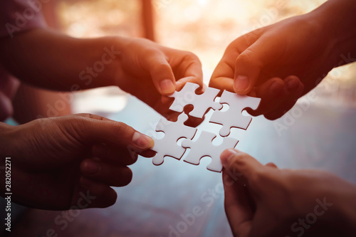Fotomural Closeup hand of business people connecting jigsaw puzzle with sunlight effect, B
