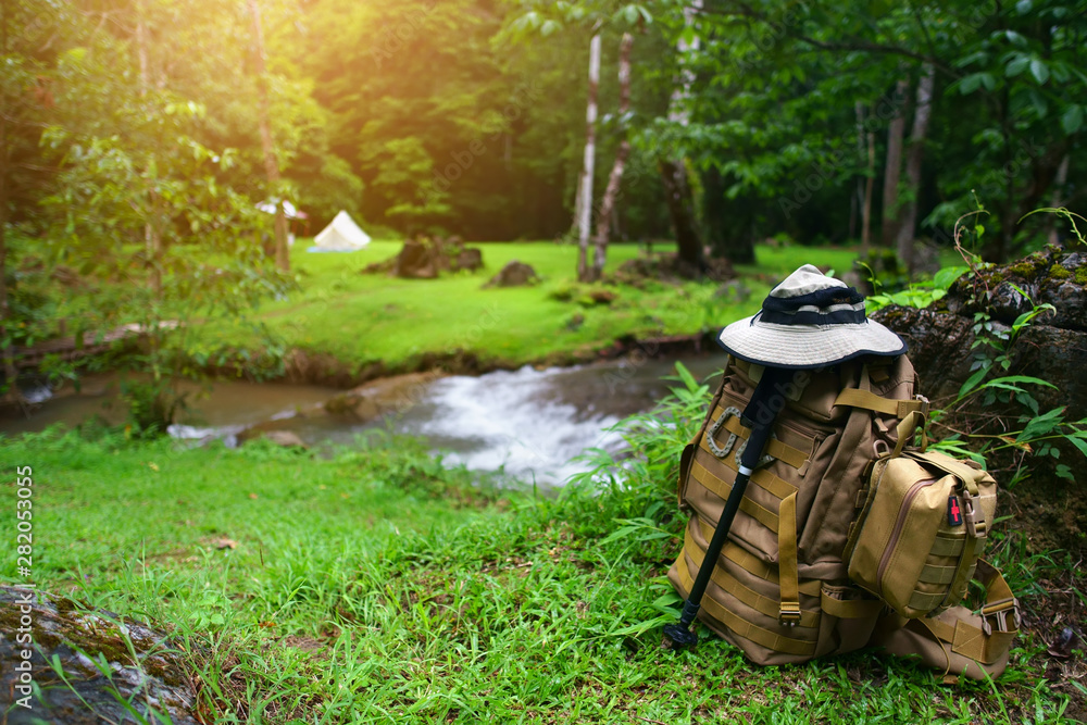 Fototapety, obrazy: backpack with SOS bag and hiking walking pole with hat for trekking and camping tent on stream with tree in green grass jungle for holiday relax and vacation travel trip with adventure nature morning