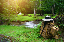 Backpack With SOS Bag And Hiking Walking Pole With Hat For Trekking And Camping Tent On Stream With Tree In Green Grass Jungle For Holiday Relax And Vacation Travel Trip With Adventure Nature Morning