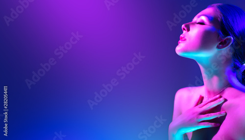 Keuken foto achterwand Beauty Fashion model woman in colorful bright neon lights posing in studio. Portrait of beautiful girl in UV. Art design colorful makeup