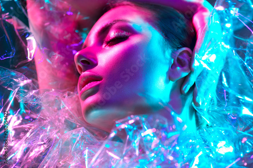 Wall Murals Beauty Fashion model woman in colorful bright neon lights posing in studio through transparent film. Portrait of beautiful sexy girl in UV. Art design colorful makeup