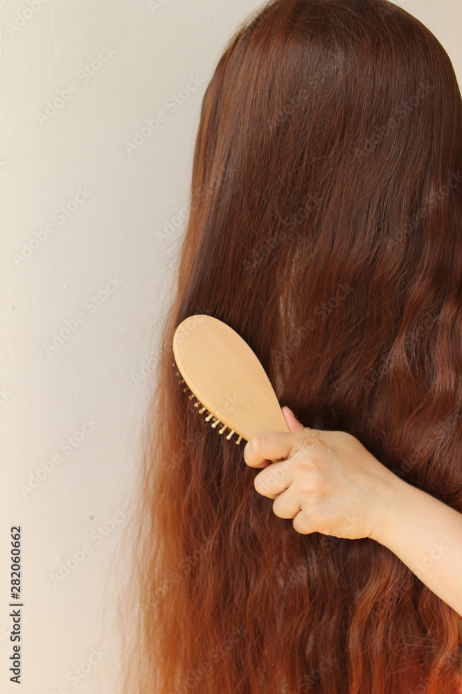 Fototapeta girl with long dark red hair combing them with a wooden comb, vertical, close-up