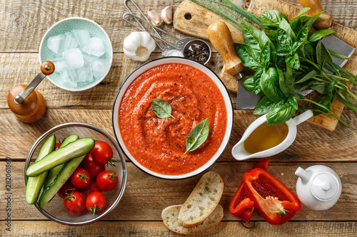 Fototapeta Gazpacho soup. Traditional spanish cold tomato soup of fresh raw vegetables with cooking ingredients on a wooden table top view obraz