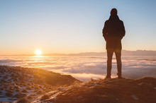 View From The Back. A Lonely Standing Man High In The Mountains Looks At The Setting Sun And The Sunset Horizon With A Valley Filled With Clouds. The Concept Of Tourism Travel And Male Loneliness