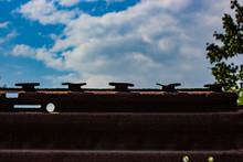 Metallic Rusty Fence With A Blue Sky.