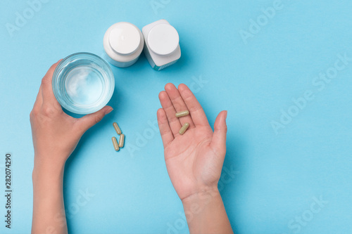 Stampa su Tela  Glass with water and food supplement in the hands of a girl on a blue background