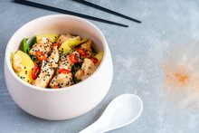 Thai Styled Bowl Salad On Grey Stone Background. Warm Salad With Sweet And Sour Chicken, Pepper Chili, Mango, Spinach. Copy Space For Design. Flat Lay Pam-asian Food