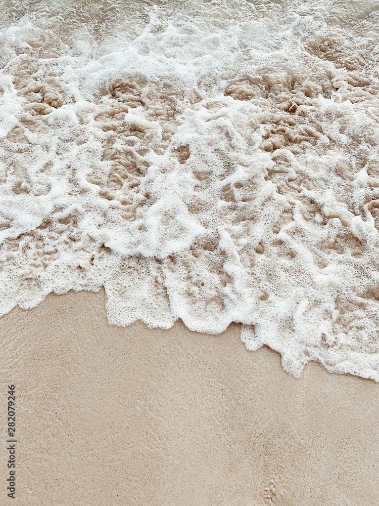 Fototapeta Beautiful tropical beach with white sand and sea with white frothy waves on Phuket, Thailand. Minimal composition with neutral colors. Summer and travel concept. Natural background.