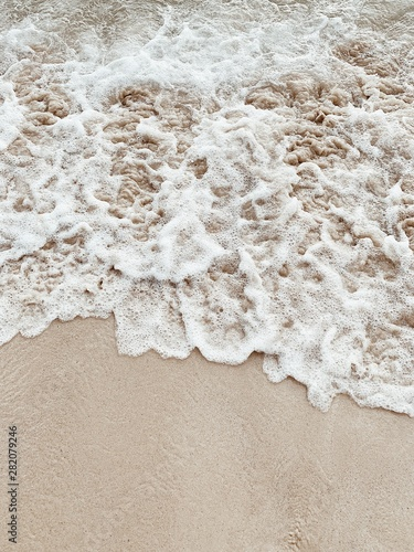 Beautiful tropical beach with white sand and sea with white frothy waves on Phuket, Thailand. Minimal composition with neutral colors. Summer and travel concept. Natural background. - fototapety na wymiar