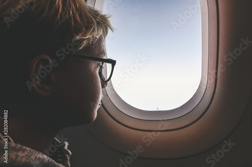 Valokuva  Boy with glasses looking clouds and sky outside the plane porthole
