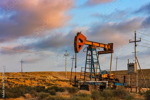 Fototapeta Oil rig pump against a colorful sunset sky obraz