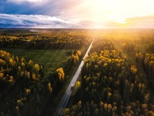 Aerial View Of Road In Beautiful Autumn Forest At Sunset In Rural Finland.