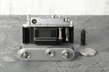 The Old Rangefinder Film Camera With On Grey Cement Background.