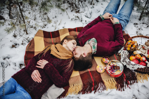 Man and girl is lying down  on a blanket at the winter picnic on the Valentines Day in a snowy park Wallpaper Mural