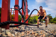 Athletic Looking Man Working Out With Rope At Street Gym Yard. Strength And Motivation. Outdoor Workout.