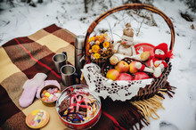 Decor On The Snow In The Winter Park. Basket With Cookies, Fruits, Hot Tea, Coffee. Happy Snowman On A Blanket At The Picnic In Forest. Merry Christmas And New Year Greeting Card With Copy-space.