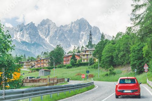 Foto auf Leinwand Olivgrun small red car on the road through mountains road trip