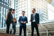 Four Asian businessmen stand to discuss real estate investment.