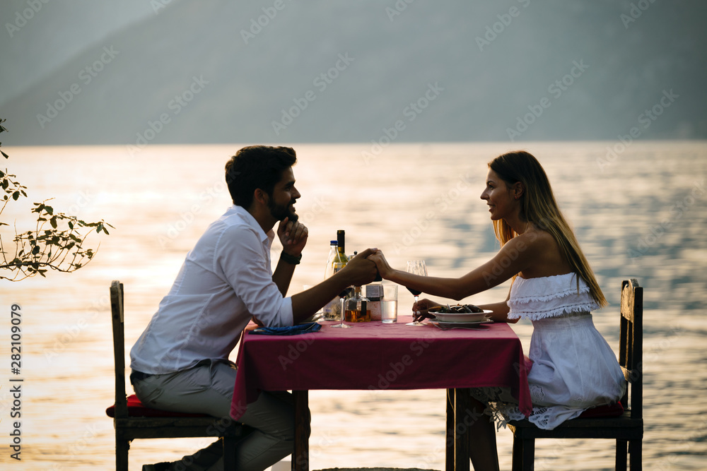 Fototapeta Couple sharing romantic sunset dinner on the beach