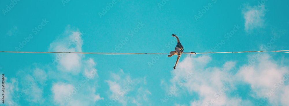 Fototapety, obrazy: Highliner on the background of blue sky.