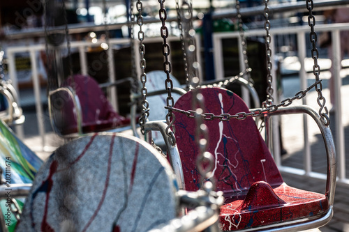 Fototapety, obrazy: Sitting on a chain. Carousel on a summer sunny day in the amusement park.
