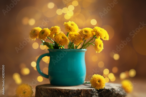 Fotografia Beautiful yellow flower in blue cup on wooden table at bokeh  background, front view
