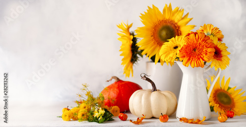 Beautiful autumn still life with bouquet of red and yellow flowers in white vases and white and orange pumpkins on wooden table, front view. Autumn concept with pumpkins and flowers.