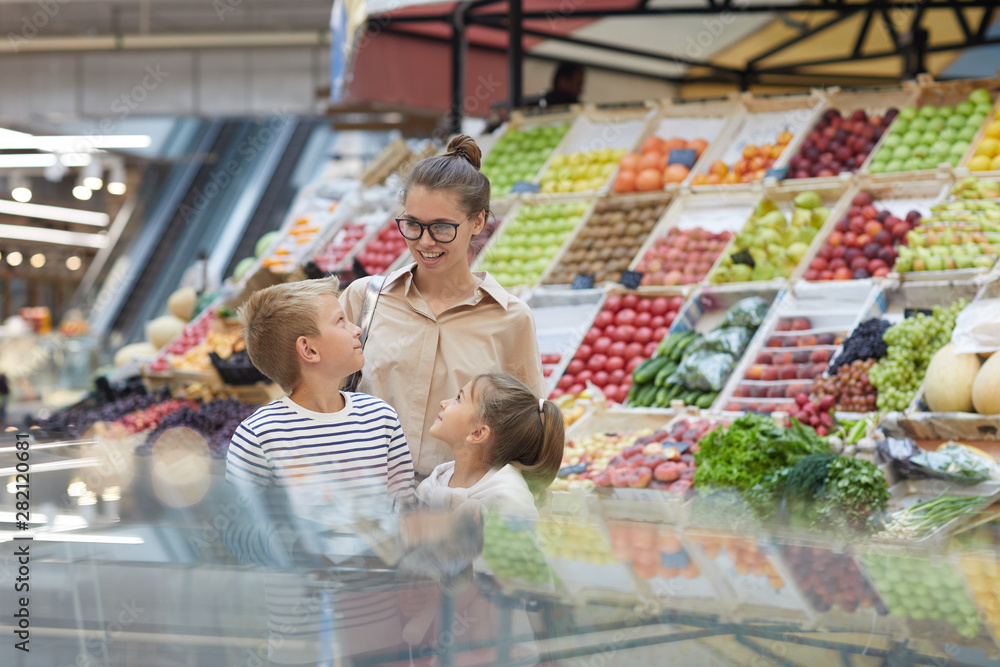Fototapety, obrazy: Portrait of contemporary young woman with two kids shopping together at farmers market, copy space