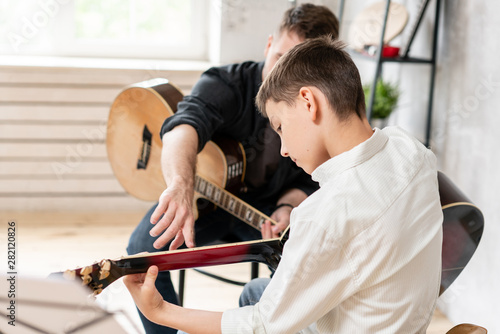 Fotografía  A personal tutor explains to his young student how to play studied chord correctly