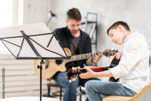 Young teenager and his older brother learining to play acoustic guitar together - 282121216