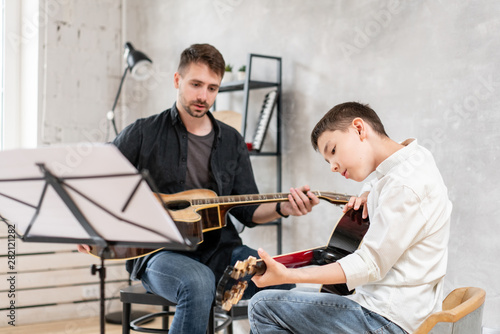Two brothers of different ages rehearsing a melody from a sheet music Fototapeta
