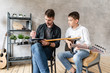Two brothers of different ages sit in chairs with electric guitars in hands and posing
