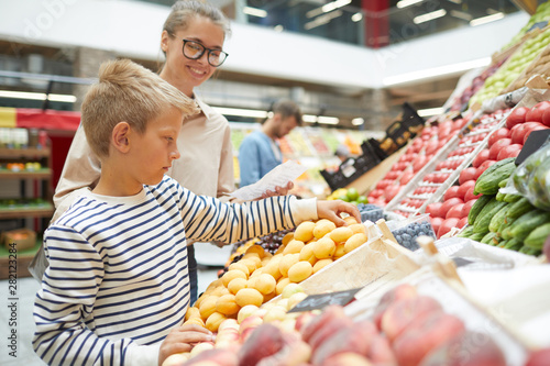 Side view portrait of teenage boy choosing fresh fruits at farmers market while grocery shopping with family, copy space - 282123284