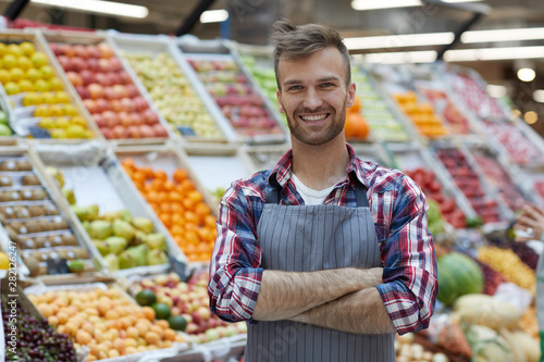 Fotografía  Waist up portrait of handsome young man working in supermarket and smiling at ca