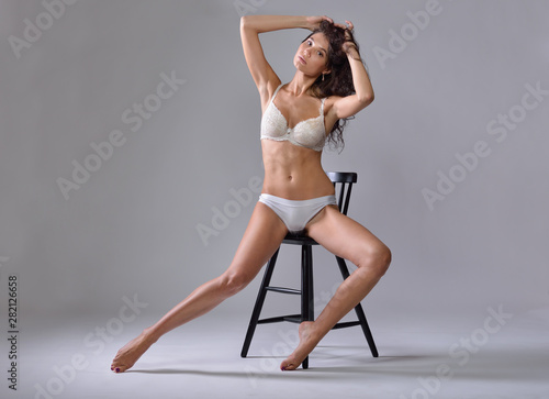 Beautiful woman in  white underwear sitting on the chair. Fototapete