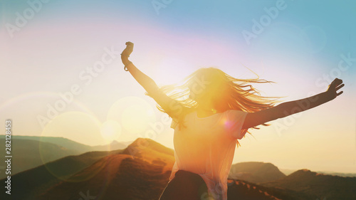 Obraz Girl on a background of mountains joyful spread her arms dancing at a height - fototapety do salonu