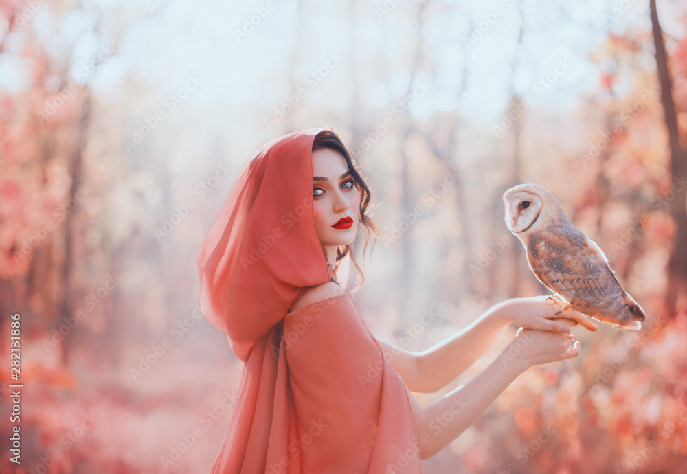 Fototapeta mystical pagan woman with covered head in peach scarf in forest, holds cute little barn owl. lady with dark curled hair, bright make-up and fair pale skin, daughter of autumn forest caring for bird